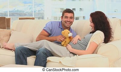 Cute couple holding a teddy bear on their sofa