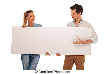 cute couple holding a white blank sign in studio