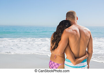 Cute couple hugging while looking at the sea