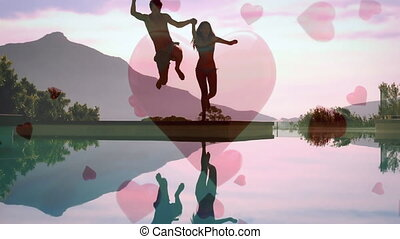 Cute couple jumping in a lake with digital hearts on the background