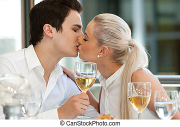 Cute couple kissing at dinner table.