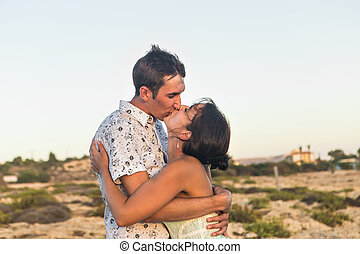 Cute couple kissing outdoors on a sunny day