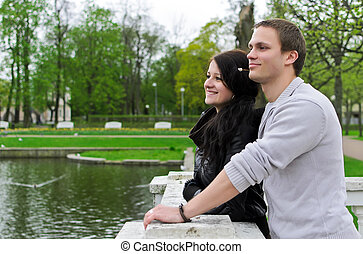 Cute couple looking at a pond in the park