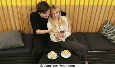Cute couple looking at a smartphone at a cafe