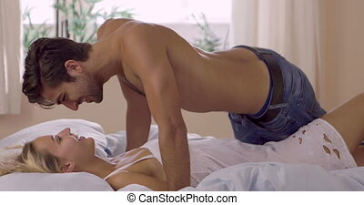 Cute couple lying on bed and kissing at home in bedroom