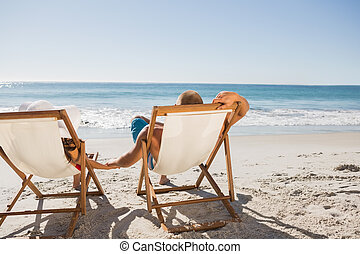 Cute couple lying on their deck chairs