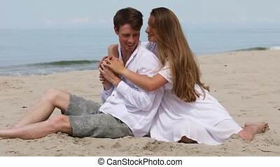 Cute couple of young lovers relax on the beach on a sunny ...