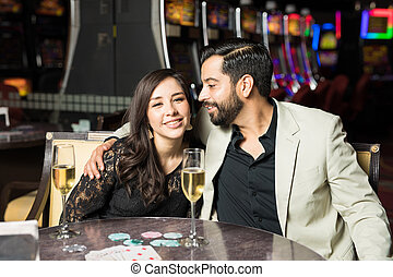 Cute couple on a casino date - Pretty young couple flirting...