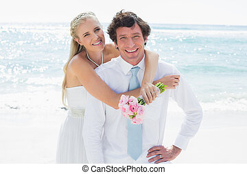 Cute couple on their wedding day smiling at camera