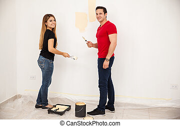 Cute couple painting a wall
