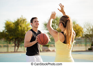 Cute couple playing basketball
