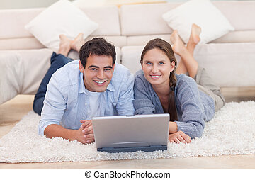 Cute couple posing with a laptop