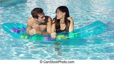 Cute couple relaxing on floating mattress in pool