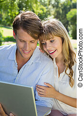 Cute couple sitting on park bench together looking at laptop