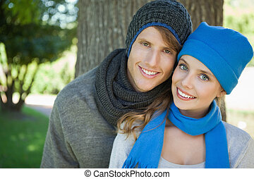 Cute couple smiling at camera in hats and scarves