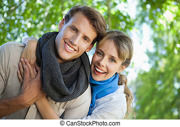 Cute couple smiling at camera in the park