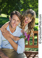 Cute couple smiling at camera in the park with girl holding flowers on a sunny day