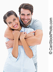 Cute couple smiling at camera on white background