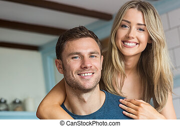 Cute couple smiling at camera at home in the kitchen