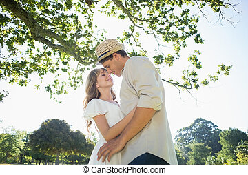Cute couple standing in the park embracing on a sunny day