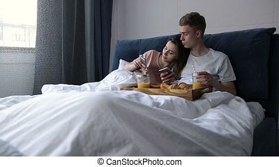 Cute couple surfing net with smartphones in bed