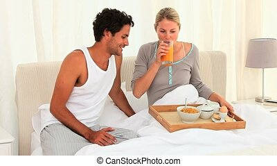Cute couple taking the breakfast on their bed