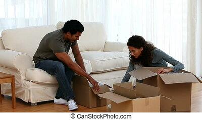 Cute couple unpacking dishes sitting in their new living room