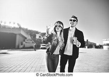 Cute couple walking at the street and drink a cocktails