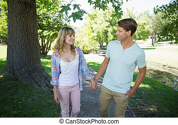 Cute couple walking hand in hand in the park