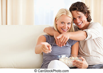 Cute couple watching TV while eating popcorn
