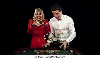 Cute couple winning and throwing chips in the air. Black