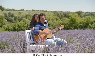 Cute couple with guitar bonding in lavender field -...