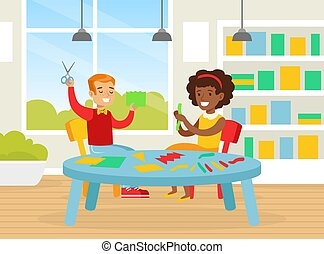 Cute Creative Kids Sitting at Table Cutting Color Paper with Scissors, Smiling Boy and Girl Crafting Together in Kindergarten Cartoon Vector Illustration