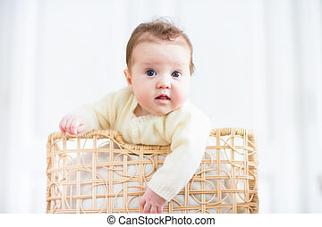 Cute curious baby watching out of a laundry basket