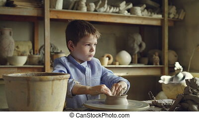 Cute curious child is making clay pot on spinning throwing...