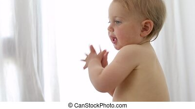 Cute curious naked baby playing at home - Side view of...