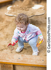 Cute curly baby girl digging in sand on a playground