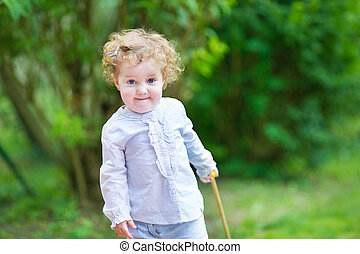 Cute curly baby girl playing in the garden