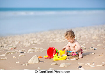 Cute curly baby girl playing with sand on a beautiful beach