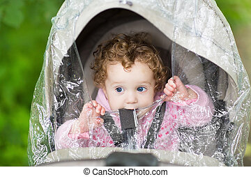 Cute curly baby girl sitting in a stroller under a plastic rain
