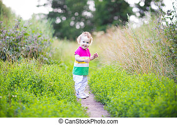 Cute curly baby girl walking in a park