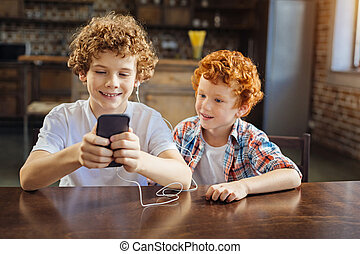 Cute curly haired brothers enjoying music together