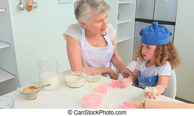 Cute curly-haired girl baking with her grandmother in the...