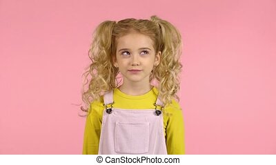 Cute curly little female kid is thoughtful and then smiling...