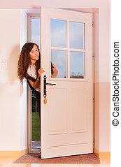 Cute curly teenage girl opening the front door