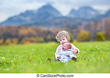 Cute curly toddler girl and her newborn baby brother playing in