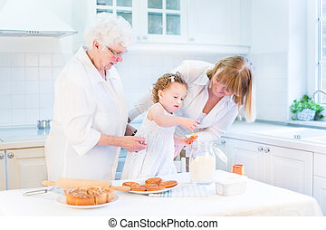 Cute curly toddler girl baking a pie with her grandmothers