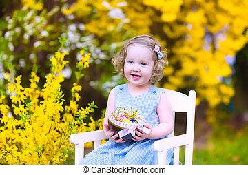 Cute curly toddler girl enjoying egg hunt in the garden