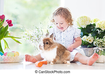 Cute curly toddler girl playing with a bunny next to flowers