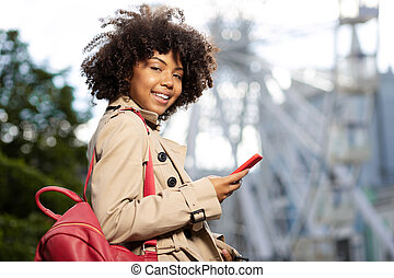Cute curly woman posing while using her phone